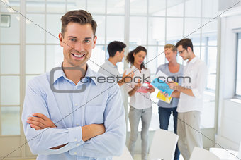 Casual boss smiling at camera in front of his team