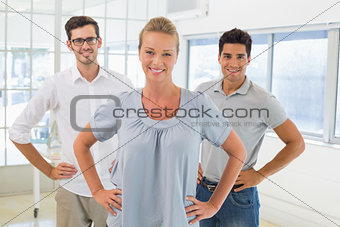 Casual business team smiling at camera with hands on hips