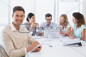 Casual businessman taking notes during meeting