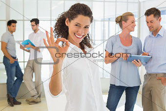 Casual businesswoman giving ok sign to camera