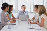 Casual boss smiling at camera dueing meeting with business team