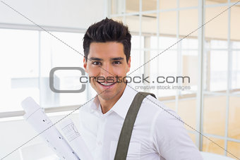 Casual handsome architect smiling at camera holding blueprint