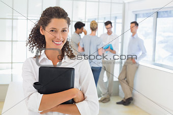 Casual businesswoman smiling at camera holding diary
