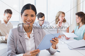 Casual businesswoman using her tablet during a meeting