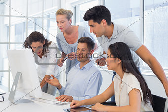 Casual businessman showing colleagues something on computer