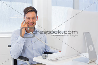 Casual businessman in wheelchair working at his desk on the phone