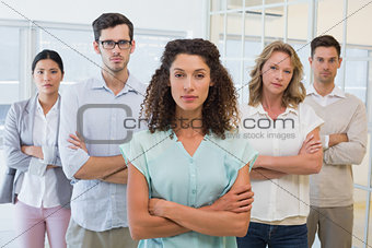 Casual business team frowning at camera with arms crossed