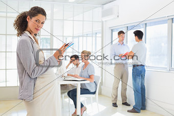 Pregnant businesswoman looking at camera with team behind her
