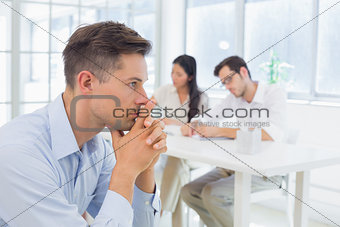 Casual businessman thinking with team behind him
