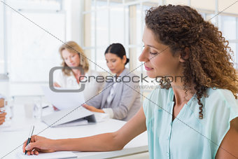 Casual businesswoman taking notes during meeting