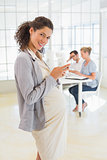Pregnant businesswoman sending text with team behind her