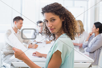 Casual businesswoman looking at camera during meeting