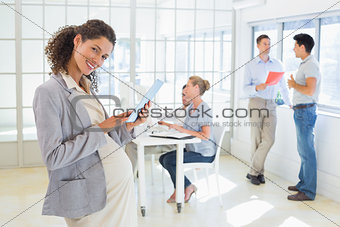 Pregnant businesswoman using tablet with team behind her