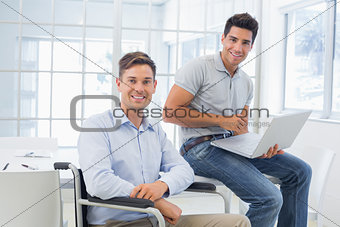 Casual businessman in wheelchair working with colleague