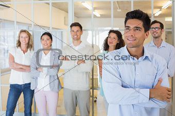 Casual boss smiling with arms crossed in front of business team