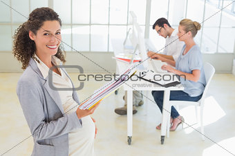 Pregnant businesswoman smiling at camera with team behind her