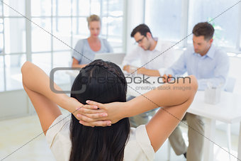 Casual businesswoman leaning back during a meeting