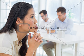 Casual businesswoman thinking during a meeting