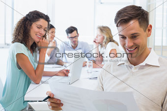 Casual businessman reading document during meeting