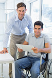 Casual businessman in wheelchair smiling at camera with colleague