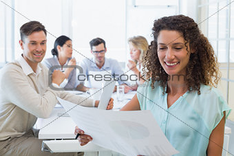 Casual businesswoman reading document during meeting