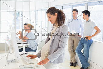 Pregnant casual businesswoman using computer