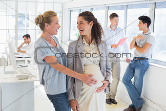 Casual businesswoman touching her pregnant colleagues belly