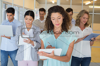 Casual boss standing in front of her team all taking notes