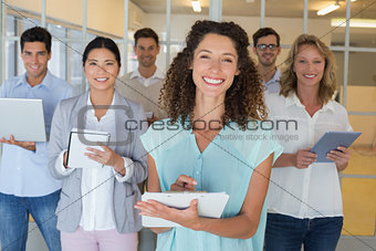 Casual boss standing in front of her team all taking notes smiling at camera