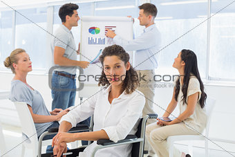 Casual businesswoman in wheelchair looking at camera during presentation