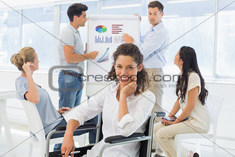 Casual businesswoman in wheelchair smiling at camera during presentation