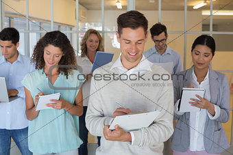 Casual boss standing in front of his team all taking notes
