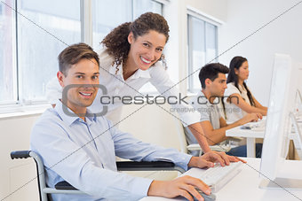 Casual businessman in wheelchair working at his desk with colleague
