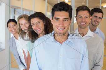 Casual business team smiling at camera together