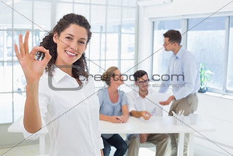 Casual happy businesswoman making ok sign to camera