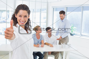 Casual happy businesswoman showing thumbs up to camera