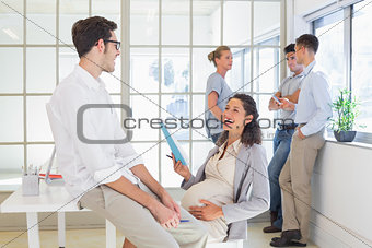 Pregnant businesswoman laughing with colleague