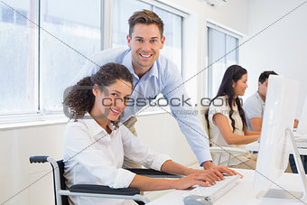 Casual businesswoman in wheelchair working at her desk with colleague