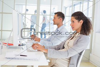 Casual pregnant businesswoman working at desk