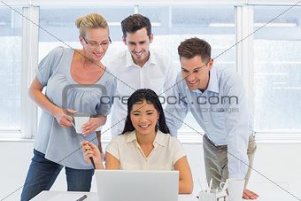 Casual business team looking at laptop together