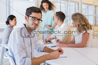 Casual businessman smiling at camera during meeting