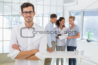 Casual businessman smiling at camera with team behind him