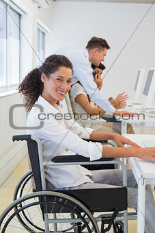 Casual businesswoman in wheelchair working at her desk
