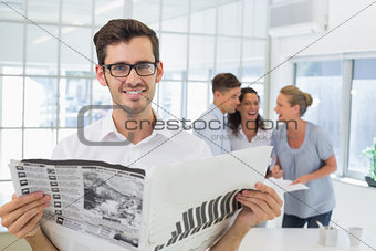 Casual businessman holding newspaper smiling at camera