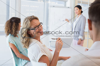 Casual businesswoman smiling at colleague during meeting