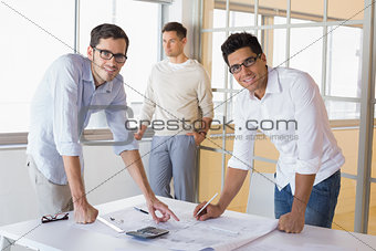 Casual architecture team working together at desk smiling at camera