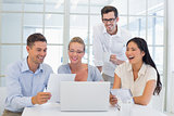 Casual business team laughing together at desk