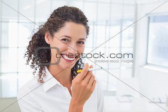 Casual businesswoman smoking an electronic cigarette