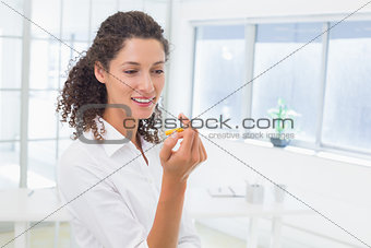 Casual businesswoman looking at her electronic cigarette