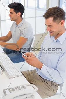 Casual businessman sending a text at his desk